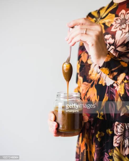 homemade salted caramel sauce on woman hand - caramelo de manteiga comida doce imagens e fotografias de stock