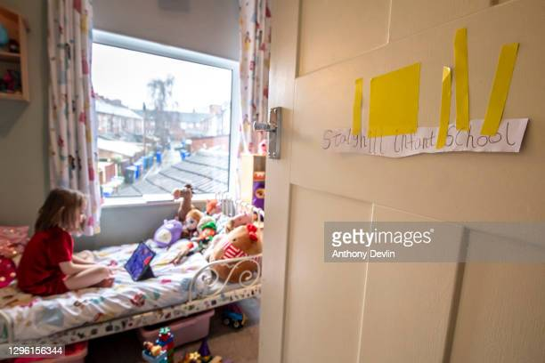 Homemade school sign is seen on the door of the photographer's daughter, Charlotte Devlin as she carries out school work online on her bed as schools...