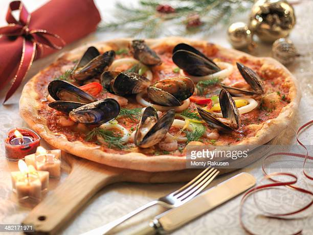 homemade seafood pizza topped with calamari, prawns and mussels with festive decorations - 魚介類 ストックフォトと画像