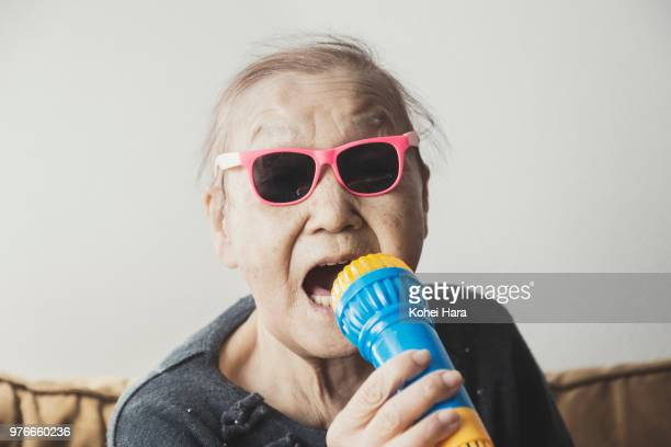 homemade senior rock singer wearing toy sunglasses - 歌う ストックフォトと画像