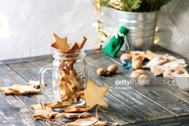 Homemade shortbread star shape sugar cookies different size in glass jar and as garland on old wooden table decorated by Christmas tree and gifts...