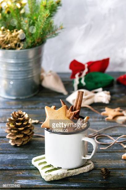 Homemade shortbread star shape sugar cookies different size in vintage mug and as garland on old wooden table decorated by Christmas tree and gifts...