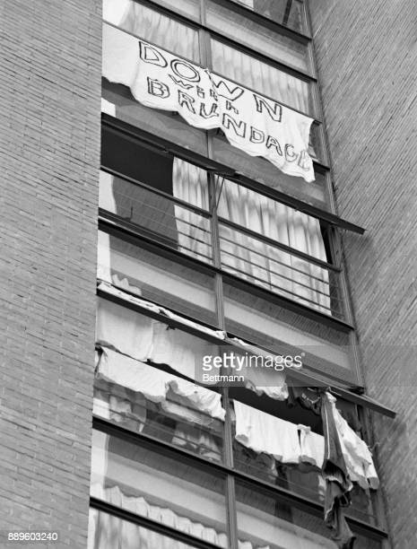 A homemade sign reading 'Down With Brundage' hangs from a window in the American dormitory at Olympic Village October 18th after the US Olympic...