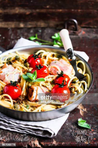 Homemade spaghetti pasta dish with bacon, roasted cherry tomatoes, capers and mint in a pan on a wooden table, selective focus
