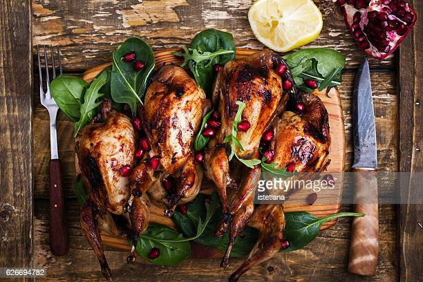 Homemade sticky roast quail served with  green salad and pomegranate seeds