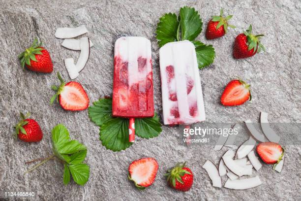 homemade strawberry coconut ice lollies with fresh strawberries and coconut slices on granite - frozen fruit stock pictures, royalty-free photos & images