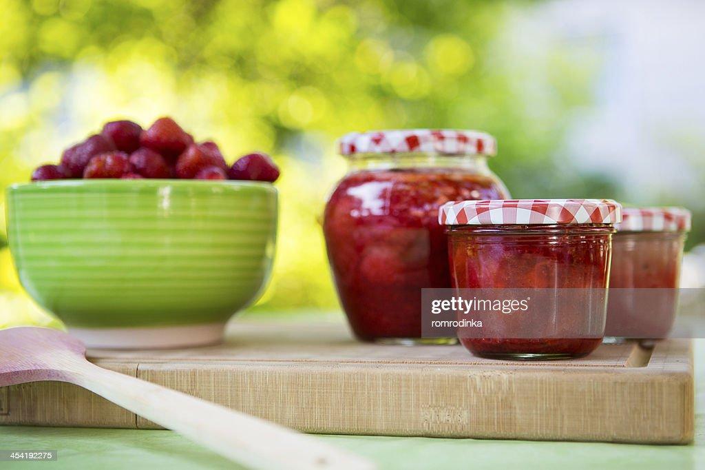 Homemade strawberry jam in different jars and fresh ripe strawbe : Stock Photo