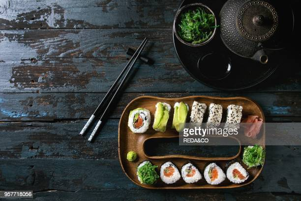 Homemade sushi rolls set with salmon sesame seeds and avocado serving in wood plate with pink pickled ginger soy sauce wasabi seaweed salad...