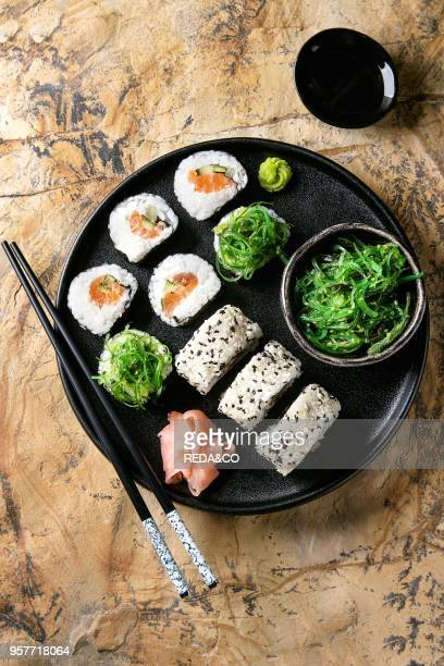 Homemade sushi rolls set with salmon sesame seeds serving in black plate with pink pickled ginger soy sauce wasabi seaweed salad chopsticks over...