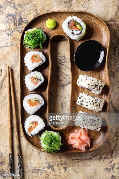 Homemade sushi rolls set with salmon sesame seeds serving in wood plate with pink pickled ginger soy sauce wasabi seaweed salad chopsticks over brown...