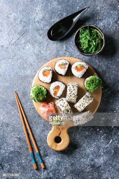 Homemade sushi rolls set with salmon sesame seeds serving on wood serving board with pink pickled ginger soy sauce wasabi seaweed salad chopsticks on...