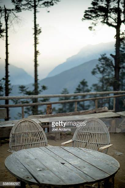 A homemade table and chairs overlook the mountains.