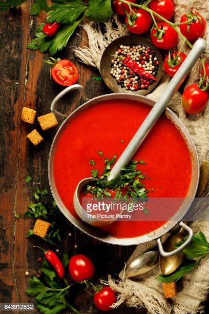 Homemade Tomato soup on wooden table, top view