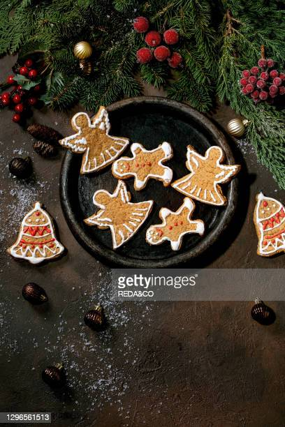 Homemade traditional Christmas gingerbread cookies with icing ornate. Gingerbread Man. Angel. Bell on ceramic plate with xmas decorations over dark...