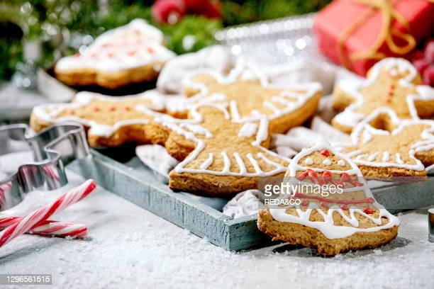 Homemade traditional Christmas gingerbread cookies with icing ornate. Gingerbread Man. Angel. Bell with xmas decorations over white bokeh background..