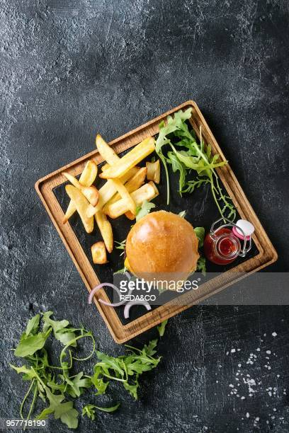 Homemade traditional hamburger with beef tomato cheese aragula served on wooden slate serving board with french fries and ketchup sauce on dark...