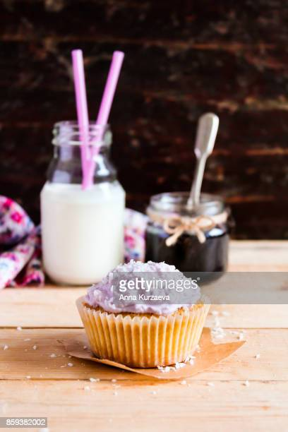 Homemade vanilla cupcakes with berry jam, coconut and cream cheese with a jar of jam and a bottle of milk on a wooden table, selective focus
