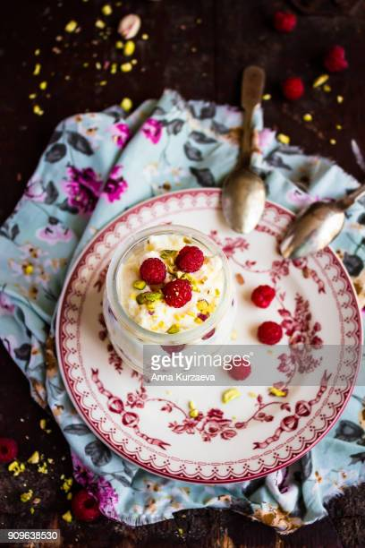 Homemade vanilla whipped cream with white chocolate, fresh raspberry and pistachios in a jar, selective focus