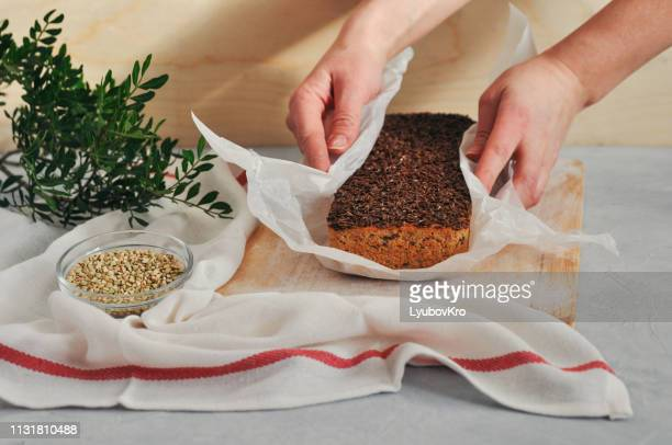 homemade vegan bread on a leaven of green buckwheat with flax seeds, sunflower in women's hands on a wooden background. healthy and proper nutrition. - buckwheat stock pictures, royalty-free photos & images