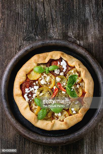 Homemade vegetable open pie galette with colorful tomatoes, tomato pesto, feta cheese and fresh basil