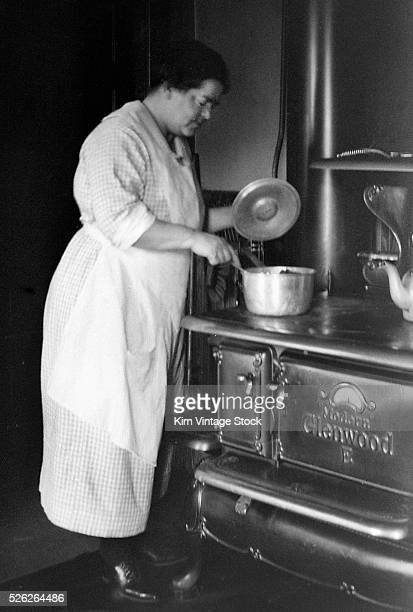 Homemaker in New England stirs a pot on a cast iron stove.