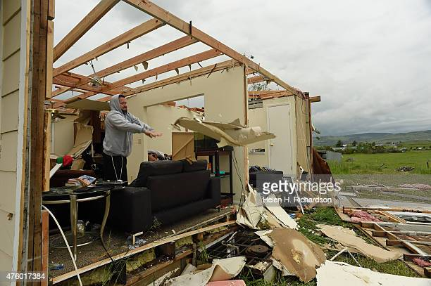Homeowner Brandon Scott throws drywall out of his living room as he tries to clean up some of the damage to his home of Brandon Scott after a tornado...