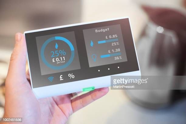 homeowner checking smart meter readings - intelligence stock pictures, royalty-free photos & images