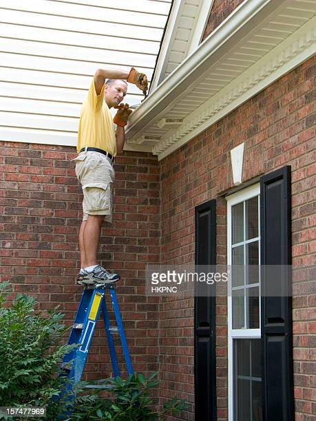 Homeowner Maintenance, Gutter Cleaning Working. Dangerously Standing On Ladder