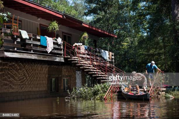 Homeowner Mike Riley left gets a hand from Brenda Smith as floodwaters from Hurricane Irma recede Sept 13 2017 in Middleburg Florida United States...