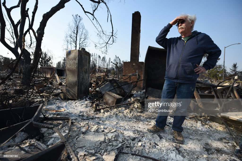 Homeowner Phil Rush looks at the remains of his home destroyed by wildfire in Santa Rosa, California, on October 11, 2017. Rush said he and his wife and dog escaped with only their medication, a bag of dog food when flames overtook their entire neighborhood on October 9. The toll from Northern California's ranging wildfires continued to grow as officials said the fires destroyed up to 2,000 structures and killed at least 17 people. / AFP PHOTO / Robyn Beck