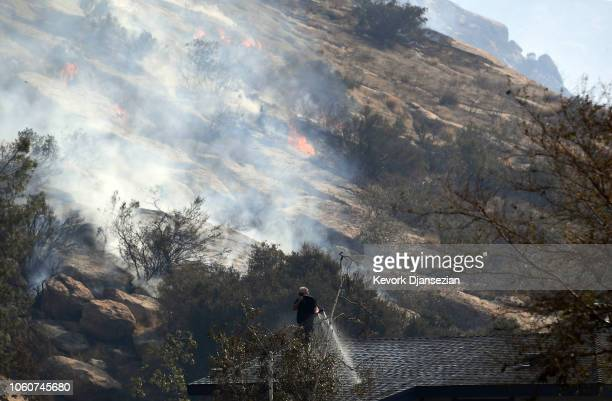 A homeowner uses a garden hose to water down his roof as the Peak Fire burns in the hills behind his home on November 12 2018 in Simi Valley...