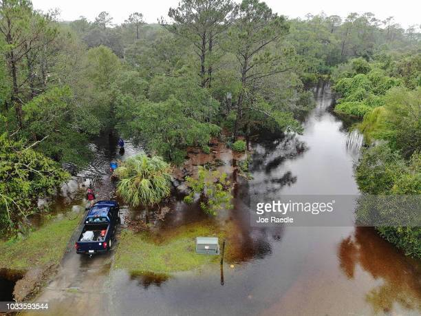 Homeowners and their friends make their way to their vehicle after checking on their home that is surrounded by flood waters after Hurricane Florence...