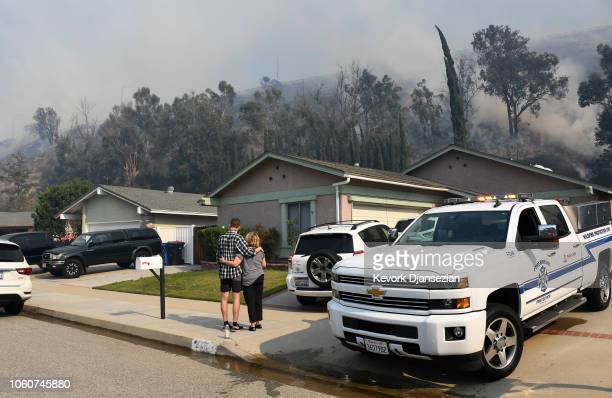 Homeowners look on as the Peak Fire burns in the hills behind their homes on November 12 2018 in Simi Valley California Multiple fires are burning...