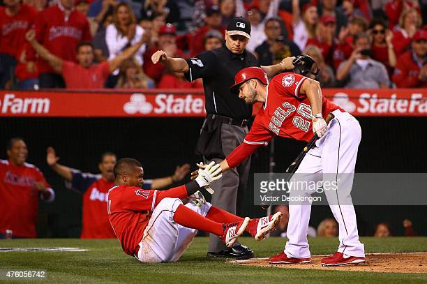 Homeplate umpire Scott Barry calls Erick Aybar of the Los Angeles Angels of Anaheim safe at home plate after a wild pitch by pitcher Tyson Ross of...