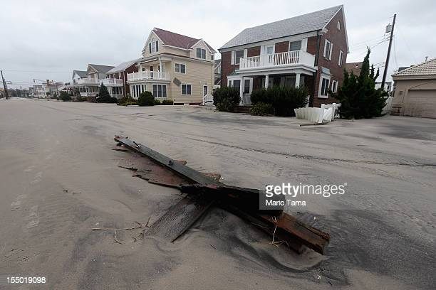 Homes and debris are seen on a street covered in beach sand flooded onto the street due to flooding from Hurricane Sandy on October 30 2012 in...