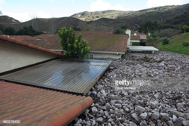 Homes are covered with rocks and mud after debris flows smashed into houses as a powerful storm that has been lashing northern California moves...
