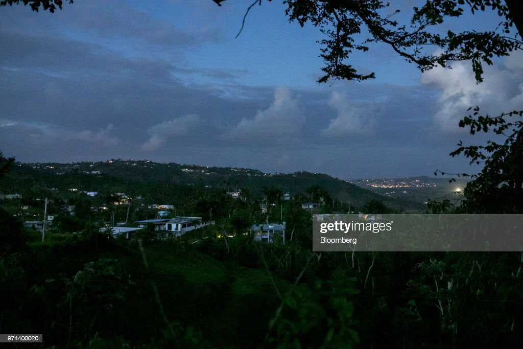 Homes, bottom left, without electricity since Hurricane Maria stand in the town of Jacanas, Yabucoa, Puerto Rico, on Friday, May 18, 2018. The bankrupt U.S. commonwealth's investment bankers last week started sounding out suitors for the eight-decade-old monopoly known asPrepa, whose rickety infrastructure was almost erased by Hurricane Maria in 2017. The halting efforts to repair the damage and improve the antiquated grid have been the central obstacle in recovery. Photographer: Xavier Garcia/Bloomberg via Getty Images
