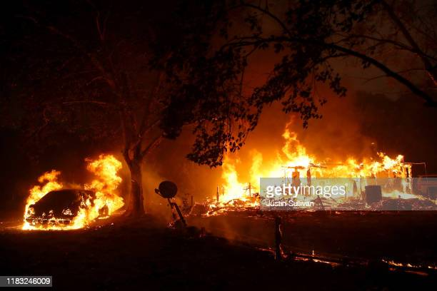 Homes continue to burn after the Kincade Fire moved through the area on October 24 2019 in Geyserville California Fueled by high winds the Kincade...