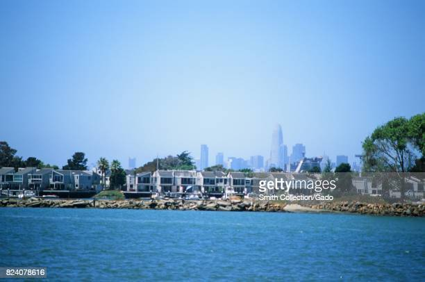 Homes on the island of Alameda California are visible over the waters of the San Francisco Bay with the skyline of San Francisco visible in the...