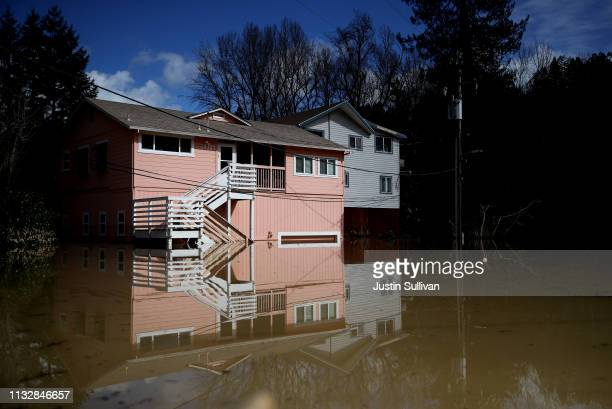 Homes sit in floodwaters in a flooded neighborhood on February 28 2019 in Guerneville California The Russian River has crested over flood stage and...
