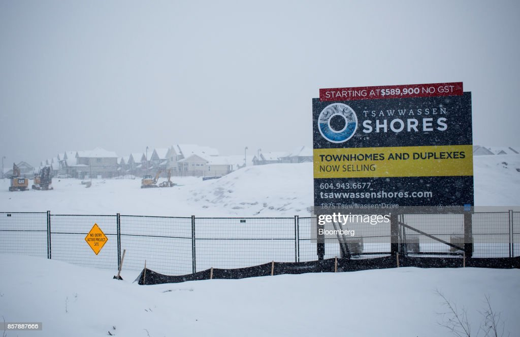 Homes under construction stand past a sign at the Tsawwassen Shores residential development in Tsawwassen, British Columbia, Canada, on Wednesday, Feb. 8, 2017. The new Tsawwassen Mills mall is one manifestation of the economic boom underway in Tsawwassen First Nation, an aboriginal community about 20 miles from both downtown Vancouver and the U.S. border. Nearby, there's a master-planned residential development where homes start at C$619,900. Photographer: Ben Nelms/Bloomberg via Getty Images