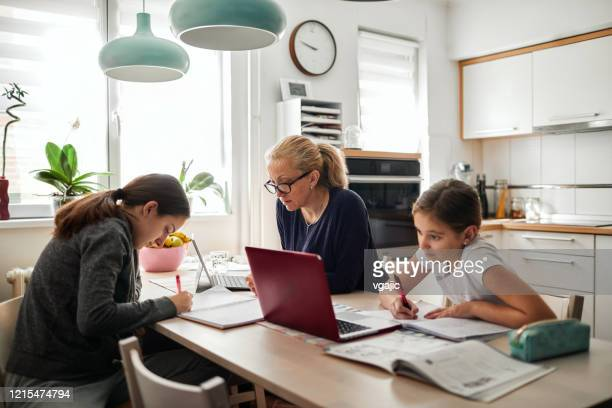 homeschooling - mother helping to her daughters to finish school homework during coronavirus quarantine - home office stock pictures, royalty-free photos & images