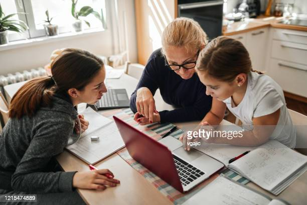 homeschooling - mother helping to her daughters to finish school homework during coronavirus quarantine - online class stock pictures, royalty-free photos & images