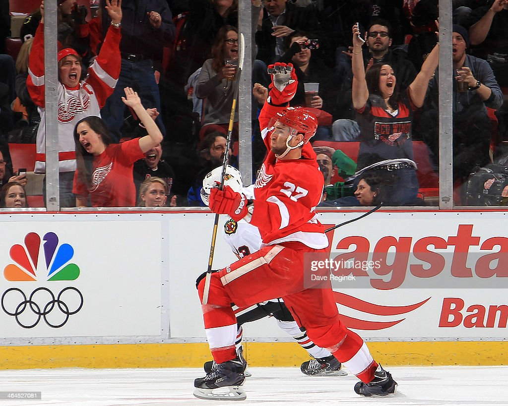 Hometown fans go crazy as Kyle Quincey #27 of the Detroit Red Wings pumps his fist after scoring a goal during an NHL game against the Chicago Blackhawks on January 22, 2014 at Joe Louis Arena in Detroit, Michigan.