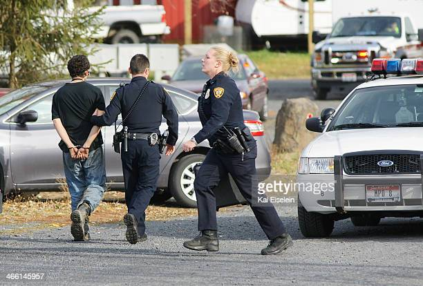 Homicide suspect Nathaniel Nisbet is escorted to a police cruiser as a female officer runs to aid the victim.