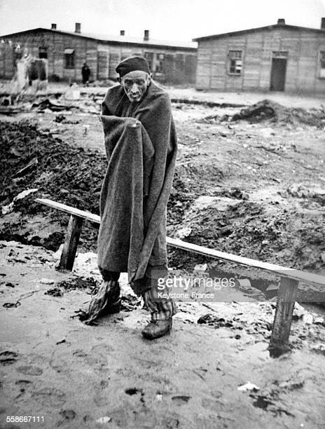 Homme amaigri, debout, enveloppé dans une couverture, dans le camp de concentration de Bergen-Belsen à Bergen, Allemagne en 1945.
