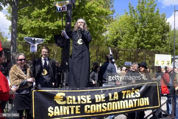Homme avec un micro déguisé en prêtre devant une banderole 'glise de la très $ainte consommation' lors de la manifestation contre la loi travail dite...