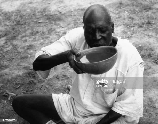 Homme buvant le dolo dans une calebasse au Burkina Faso