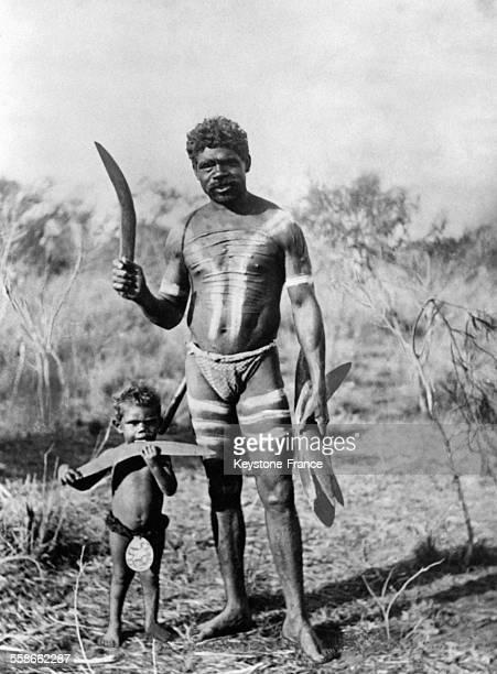 Homme et petit garçon aborigènes portant des boomerangs en Australie circa 1930