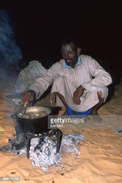 Homme nomade cuisinant un ragout de mouton dans le desert en Mauritanie en novembre 2000